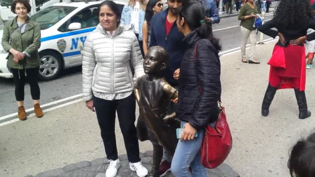 a bronze statue of a urinating dog was placed near the fearless girl statue the dog statue was later removed broll and an interview with robin krych... - kampf der geschlechter konzept stock-videos und b-roll-filmmaterial