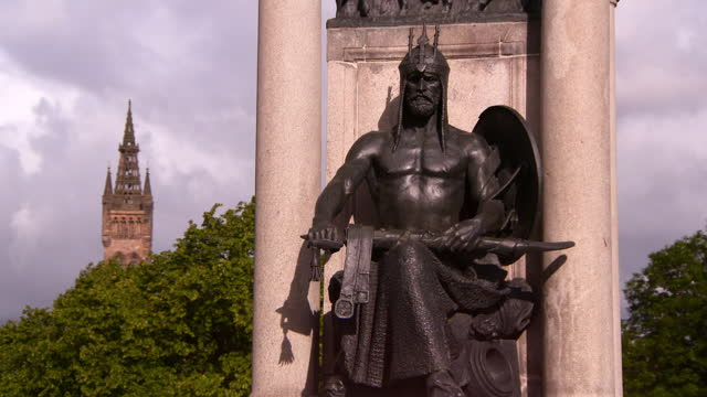 bronze statue of barbarian warrior sitting on marble plinth in front of green trees and distant sandstone bell tower - glasgow, scotland - weaponry stock videos & royalty-free footage
