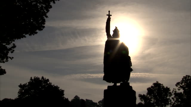 a bronze statue of king alfred the great in winchester stands in silhouette before the sun. available in hd. - 英国ハンプシャー点の映像素材/bロール
