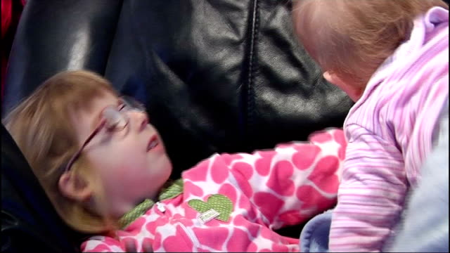 Brooke lying on sofa and cuddling baby sister