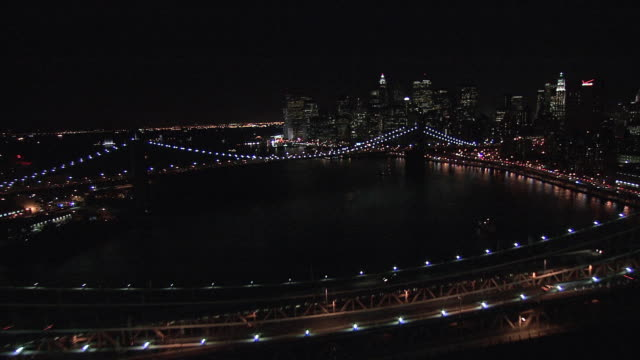stockvideo's en b-roll-footage met aerial brooklyn and manhattan bridges over the east river at night, with car headlights crossing / new york city, new york, united states - b roll
