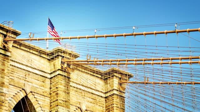 brooklyn bridge und die amerikanische flagge - manhattan brücke stock-videos und b-roll-filmmaterial