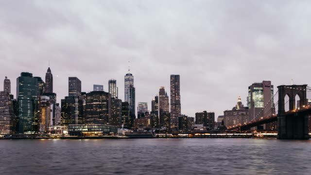 T/L PAN Brooklyn Bridge and Manhattan skyline, Dusk to Night Transition / New York