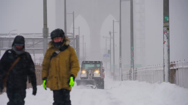 brooklyn bridge during a major winter snowstorm, amidst the pandemic of covid-19 in lower manhattan, new york city on february 01, 2021. - plough stock videos & royalty-free footage