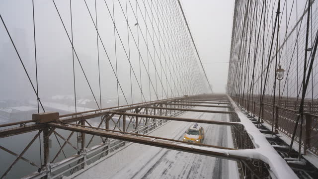 brooklyn bridge during a major winter snowstorm, amidst the pandemic of covid-19 in lower manhattan, new york city on february 01, 2021. people walk... - yellow taxi stock videos & royalty-free footage