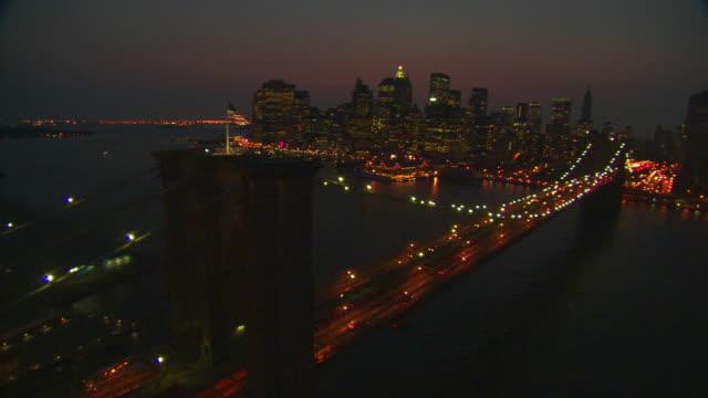 LOW AERIAL, Brooklyn bridge illuminated at night, New York City, New York, USA