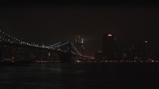 vídeos de stock, filmes e b-roll de ws brooklyn bridge illuminated at night with downtown skyline in background / new york city, new york, usa - baixo manhattan
