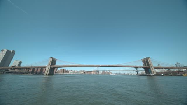 brooklyn bridge, manhattan bridge, williamsburg bridge and city skylines from water - hängebrücke stock-videos und b-roll-filmmaterial