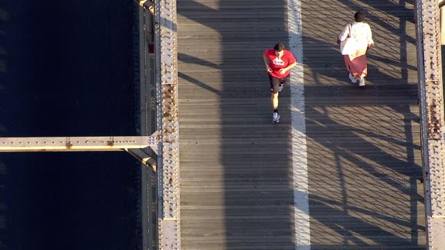 brooklyn bridge pedestrian walkway unidentifiable jogger people traffic in lanes slight reframe passing american flag on top of bridge pillar of... - brooklyn bridge stock videos & royalty-free footage