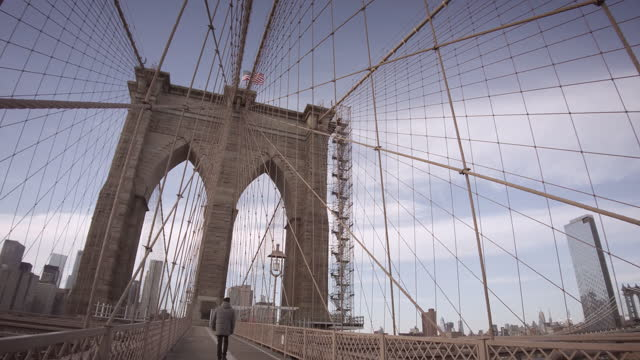 brooklyn bridge with nyc skyline with one world trade center and us flag. filmed during the coronavirus pandemic . people are wearing protective face... - dramatic sky stock videos & royalty-free footage