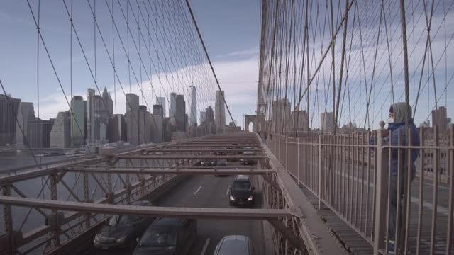 brooklyn bridge with nyc skyline with one world trade center . filmed during the coronavirus pandemic . people are wearing protective face masks. the... - yellow taxi stock videos & royalty-free footage