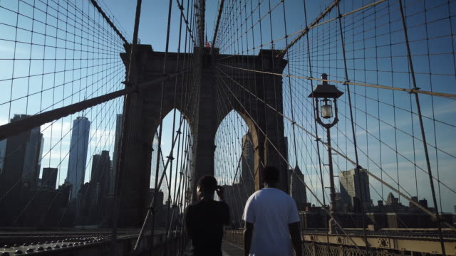 brooklyn bridge with us flag on half-mast during coronavirus pandemic - suspension bridge stock videos & royalty-free footage
