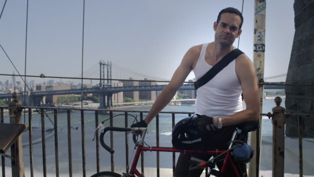 Brooklyn ciclyst posing for the camera with the Manhattan Bridge behind him