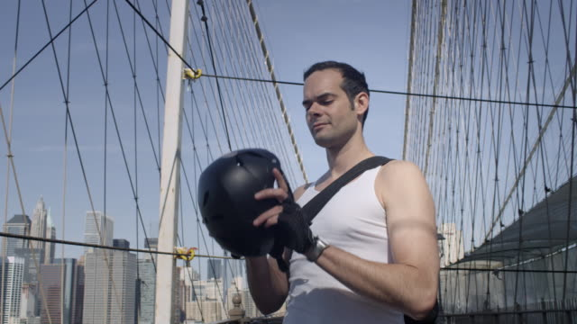Brooklyn cyclist puts on his helmet and rides away.