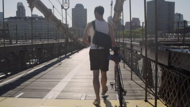 Brooklyn cyclist walking his bike over the Brooklyn Bridge