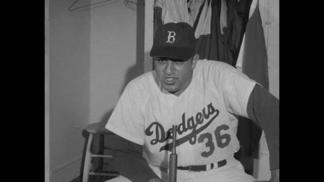 Brooklyn Dodger players in locker room / Newcombe in underwear sits on bench talking to trainer / Newcombe with uniform on sits on bench looks at...