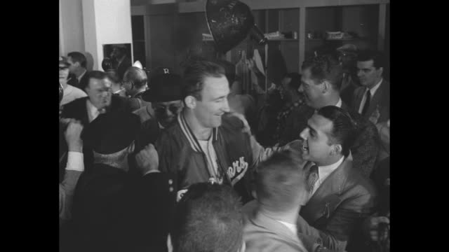 Brooklyn Dodgers enter locker room after winning the World Series against the New York Yankees / Dodger players celebrate / CU Gil Hodges smiling /...