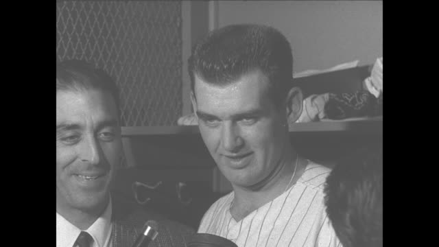 Brooklyn Dodgers pitcher Sal Maglie wearing a suit stands next to New York Yankees pitcher Don Larsen who discusses pitching his nohitter perfect...