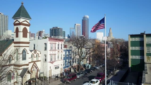 brooklyn neighborhood with american flag - aerial drone - elementary school building stock videos & royalty-free footage