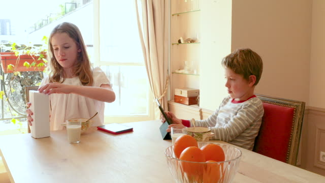 a brother and a sister having their breakfast together with digital tablets, morning - carton stock videos & royalty-free footage