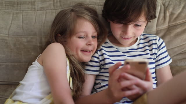 a brother and a sister playing with a smartphone - childhood stock videos & royalty-free footage