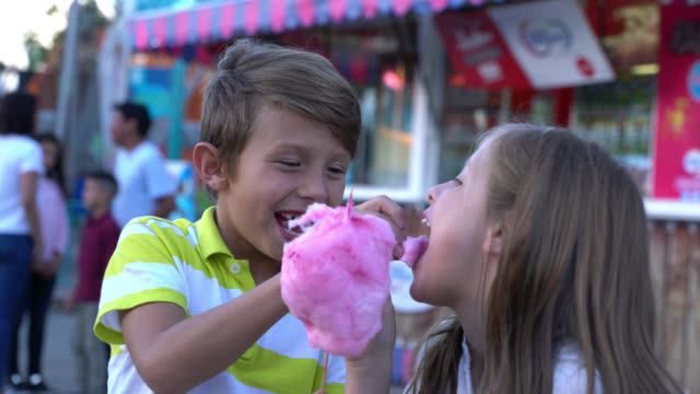 Brother and sister at a fun fair sharing cotton candy and pop corn having a great time