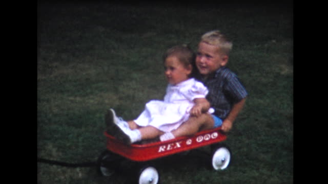stockvideo's en b-roll-footage met 1958 brother and sister being pulled in red wagon - brother