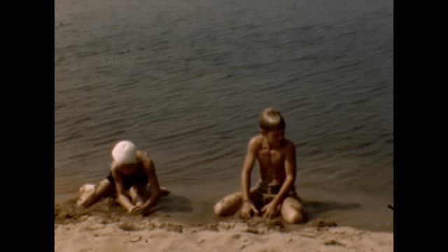 vidéos et rushes de 1953 brother and sister building sand castles - frère