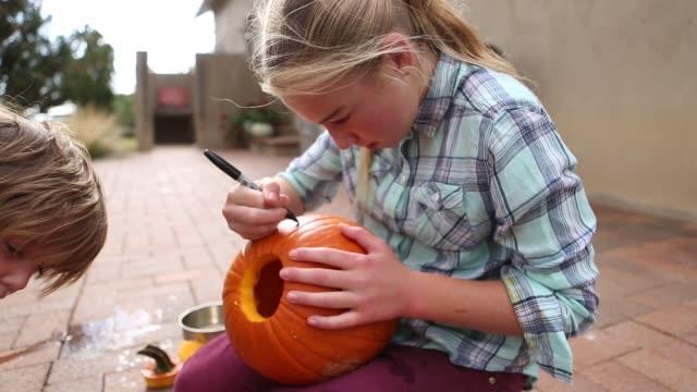 brother and sister carving pumpkins - タータンチェック点の映像素材/bロール