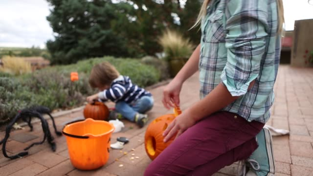 brother and sister carving pumpkins