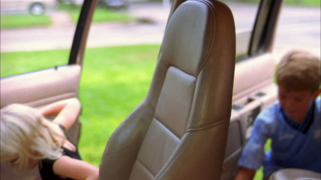 vidéos et rushes de a brother and sister climb into an suv and the sister puts on her seat belt. - justaucorps