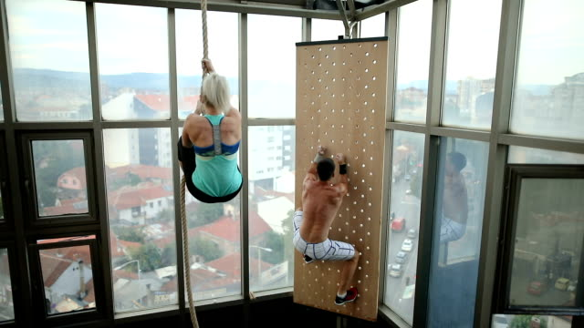 brother and sister climbing thick rope during fitness exercises - clambering stock videos & royalty-free footage