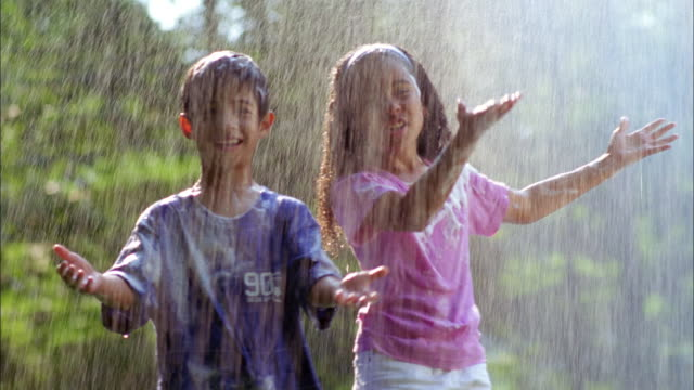 a brother and sister covered in soap play in a spray of water. - sprinkler stock videos and b-roll footage