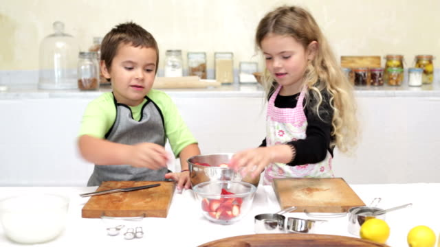 brother and sister cutting strawberries - crumble dessert stock videos and b-roll footage