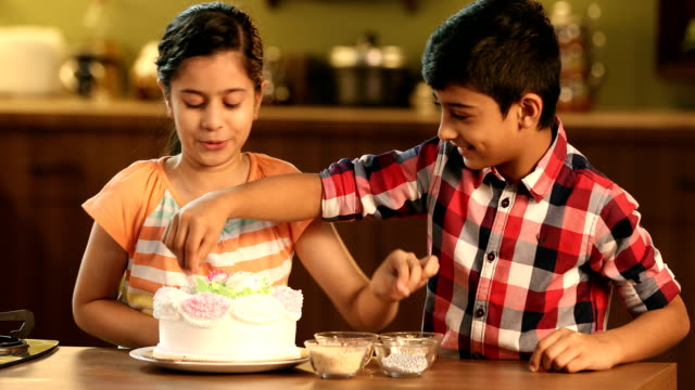 ms brother and sister decorating cake in kitchen / delhi, india - enjoyment stock videos & royalty-free footage
