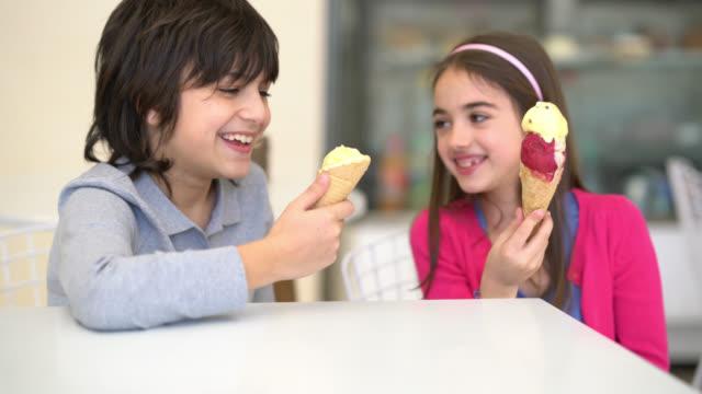vídeos y material grabado en eventos de stock de hermano y hermana disfrutando de un helado en la heladería mirando muy feliz hablando y sonriendo - cuchara de helado