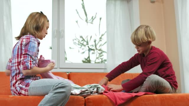 hd :dolly 兄と妹折りたたみ式ランドリー - たたむ点の映像素材/bロール