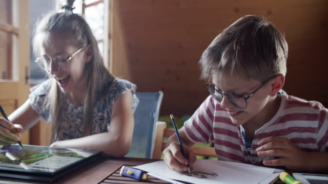 brother and sister having fun drawing at home - crayon stock videos & royalty-free footage