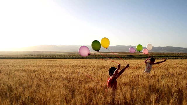 slow-mot brother and sister holding balloons and running - middle east stock videos & royalty-free footage