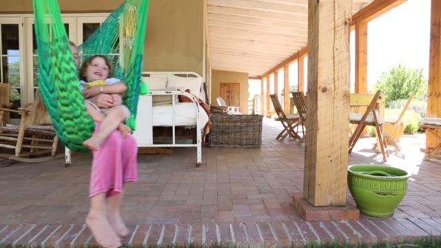 stockvideo's en b-roll-footage met brother and sister in hammock - schommelen schommelstoel