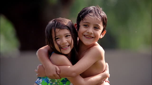 a brother and sister in their swimsuits share a hug. - embracing stock videos & royalty-free footage