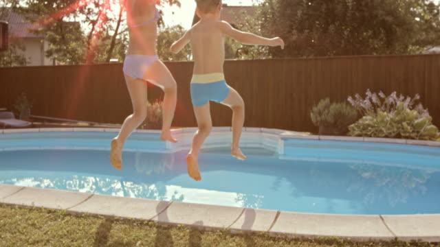 slo-mo ds bruder und schwester springen in pool - zaun stock-videos und b-roll-filmmaterial