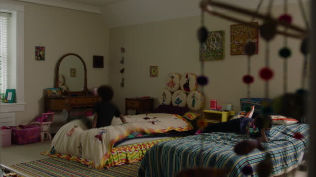 Brother and sister jumping on their bed in bedroom at home