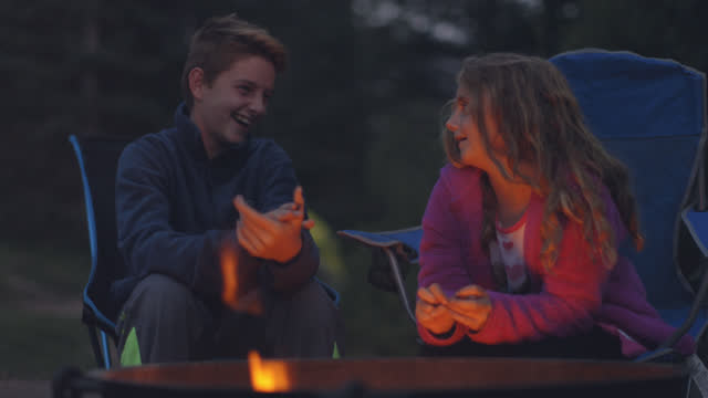 brother and sister laugh, clap, and tease each other in portable folding chairs by fire pit on family camping trip. - naturpark stock-videos und b-roll-filmmaterial