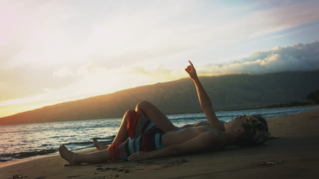 brother and sister laying on the beach. - brother stock videos & royalty-free footage
