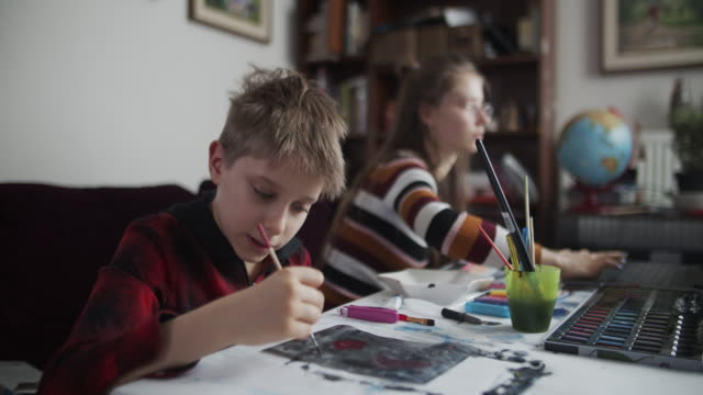 Brother and sister learn painting at home