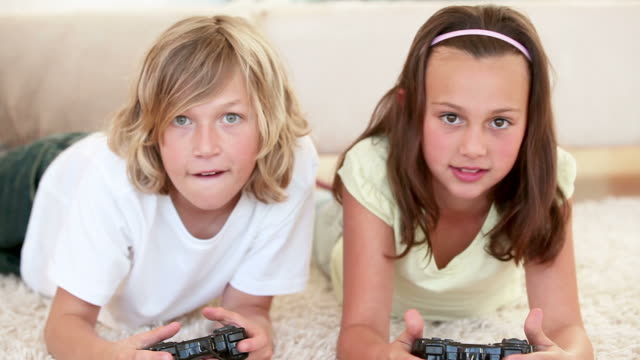 vídeos de stock, filmes e b-roll de brother and sister lying while playing video games - olhos verdes
