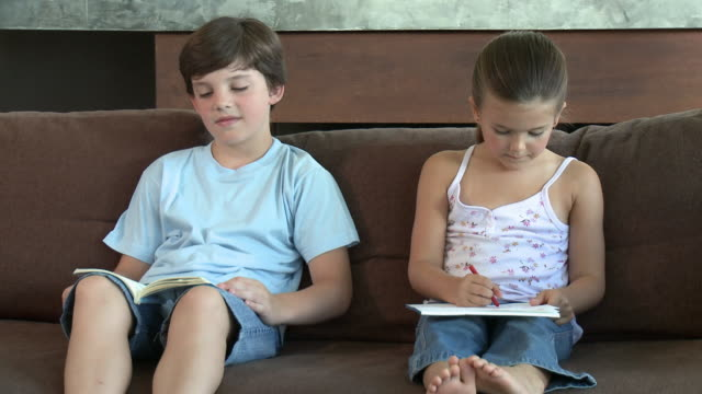 Brother and sister on sofa, reading and drawing