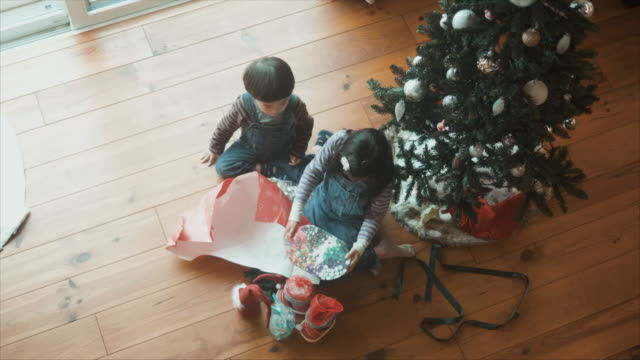 brother and sister opening christmas presents - unwrapping stock videos & royalty-free footage