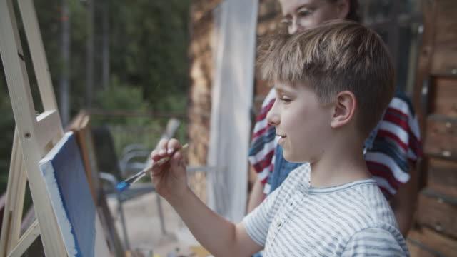 stockvideo's en b-roll-footage met het schilderen van de broer en van de zuster op canvas - 10 11 jaar